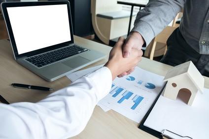 Deux hommes négocient une assurance de prêt immobilier